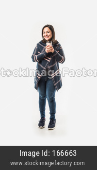Indian Lady / woman in winter wear having or drinking hot coffee or tea in carry cup, standing isolated over white background