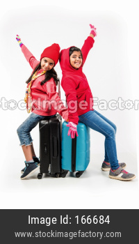Two Indian girls with suitcase while wearing warm cloths, ready for winter holidays