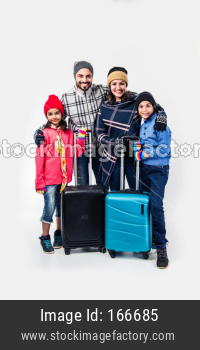 Indian family with suitcase while wearing warm cloths, ready for winter holidays