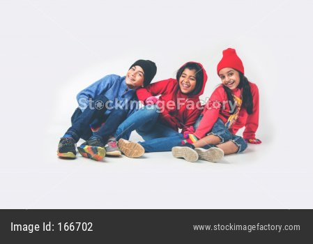 Three Indian /asian kids in winter wear sitting against white background and having fun