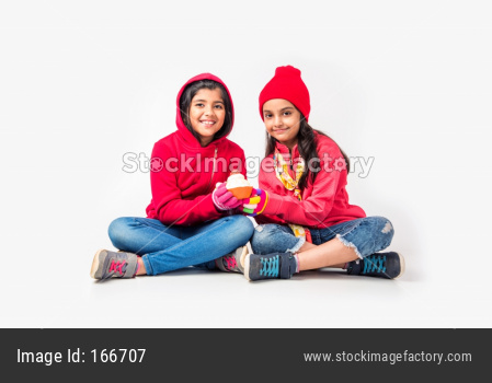Two Indian little girls in warm cloths sitting and playing against white background