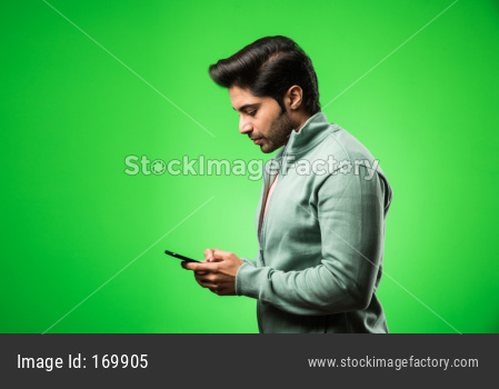 Indian / Asian man with smartphone, standing isolated over green background