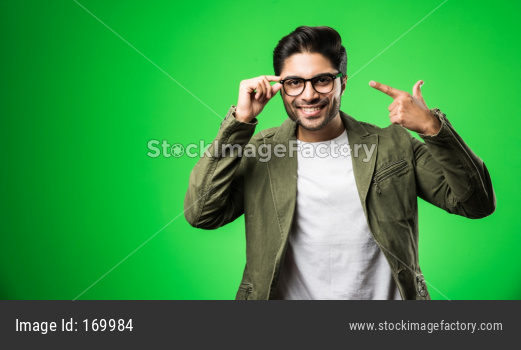 Indian man showing eye glasses, wearing t-shirt and jacket, standing isolated over green background