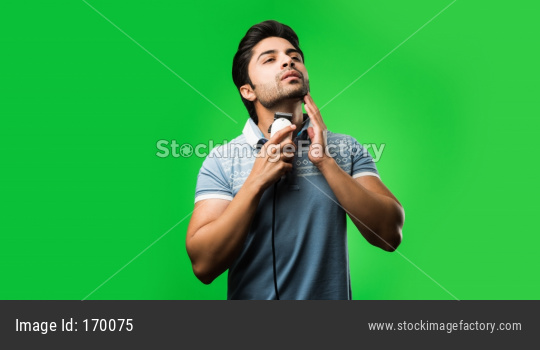 Indian / asian man shaving beard with Electric trimmer or clipper standing isolated over green background
