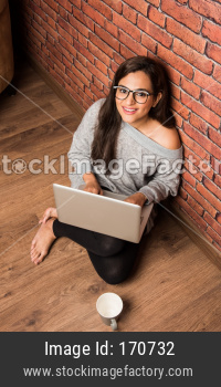 Indian girl with laptop sitting on wing chair against red brick wall