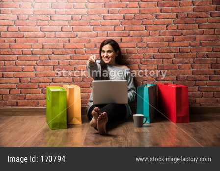 Indian girl shopping with debit / Credit card and laptop while sitting over wooden floor against red brick wall