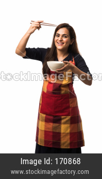 Indian Female Cook with apron holding empty bowl with chopsticks, eating or showing, standing isolated over white background