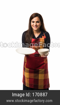 Indian Woman chef wearing apron and holding empty ceramic dinner plate and bowl