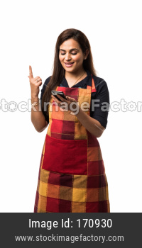Indian woman / female chef in apron using smartphone while standing isolated over white background
