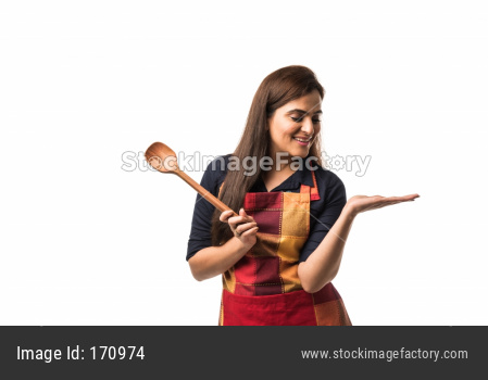 Indian / asian woman chef wearing Apron and holding wooden spatula while standing isolated over white background