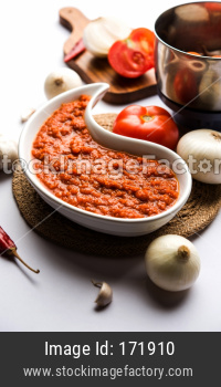 onion tomato masala or puree for indian gravy, served in a bowl with raw tamatar, pays and lehsun and red chilli, selective focu