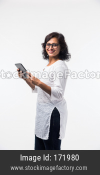 indian lady/women using tablet pc while standing isolated over white background, selective focus