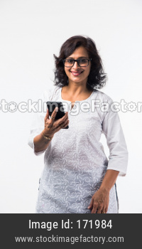 Indian mid age lady using smartphone / mobile handset while standing isolated over white background