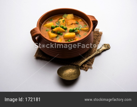 Aloo Curry Sabzi made using boiled potato with green peas. Served in a bowl or karahi, selective focus