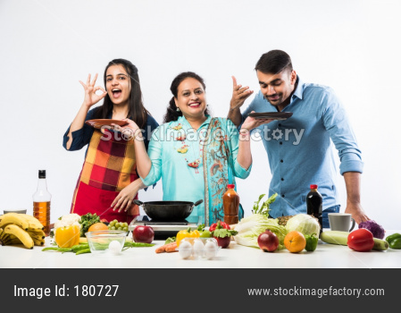 Indian Mother or Sister making food for young kids in kitchen