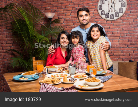 Indian young Family of four eating food at dining table