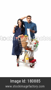Indian couple shopping with cart or trolly full of grocery, fruits