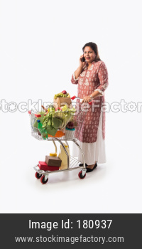 Indian mid age woman with shopping cart or trolly full