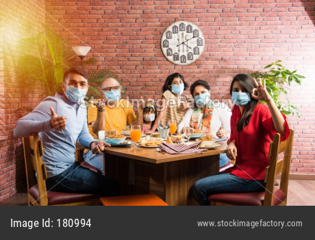 Indian Family eating food in restaurant wearing face mask after corona outbreak or unlock