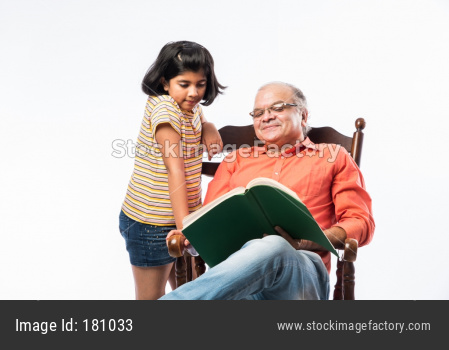 Grandfather reading book for grand daughter while sitting on rocking chair