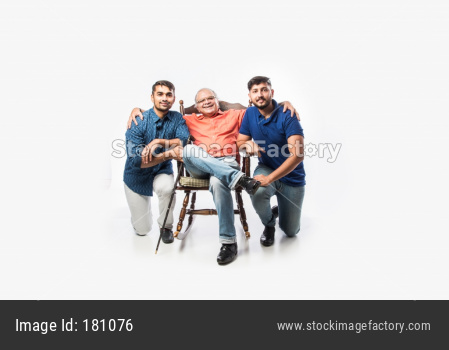 Indian old man or father with young son and daughter, sitting over rocking chair