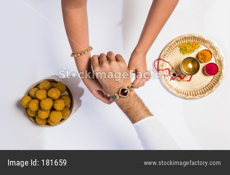 Closeup picture of girl's hand tying Rakhi thread to brother