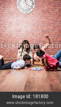 Indian family playing board games like chess, ludo or snakes and ladder