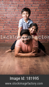 Indian kids playing riding on back with father