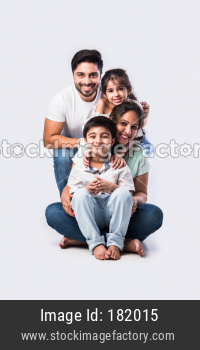 Portrait of happy young Indian family of four against white background