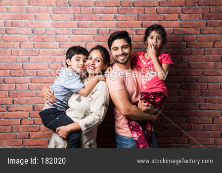 Portrait of happy young Indian family of four against brick wall
