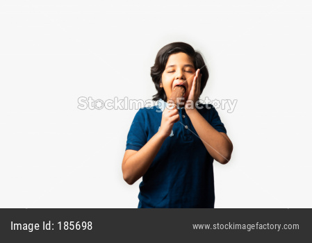 Indian kid or boy eating ice cream in cone or choco bar